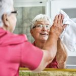Elderly woman smiling doing spring cleaning smiles as she wipes a mirror
