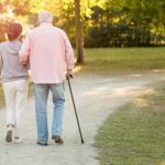 senior with cane walking with young woman